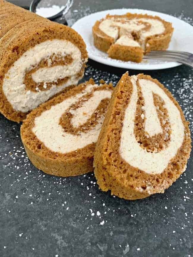easy pumpkin roll with mascarpone cream filling sliced and sitting on a black counter with powdered sugar sprinkled on it