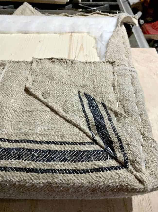 stapling grain sack on lid of storage ottoman