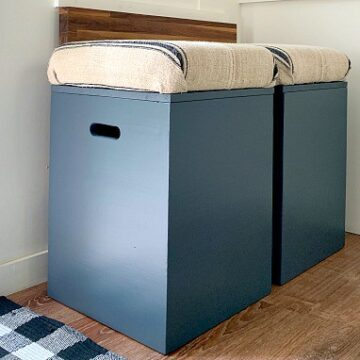 2 navy DIY storage ottomans lined up against wall in RV