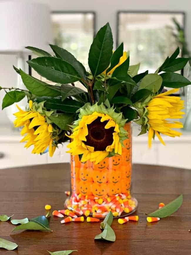 fun fall centerpiece DIY with sunflowers and foliage in the middle of a table
