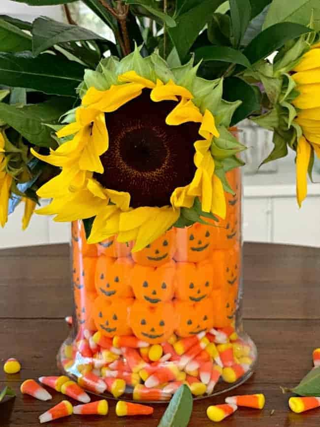 fall halloween candy centerpiece with sunflowers and foliage in the middle of a table