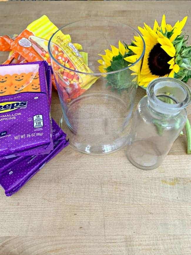 supplies to make a fall centerpiece including Peeps, candy corn, glass vases and sunflowers