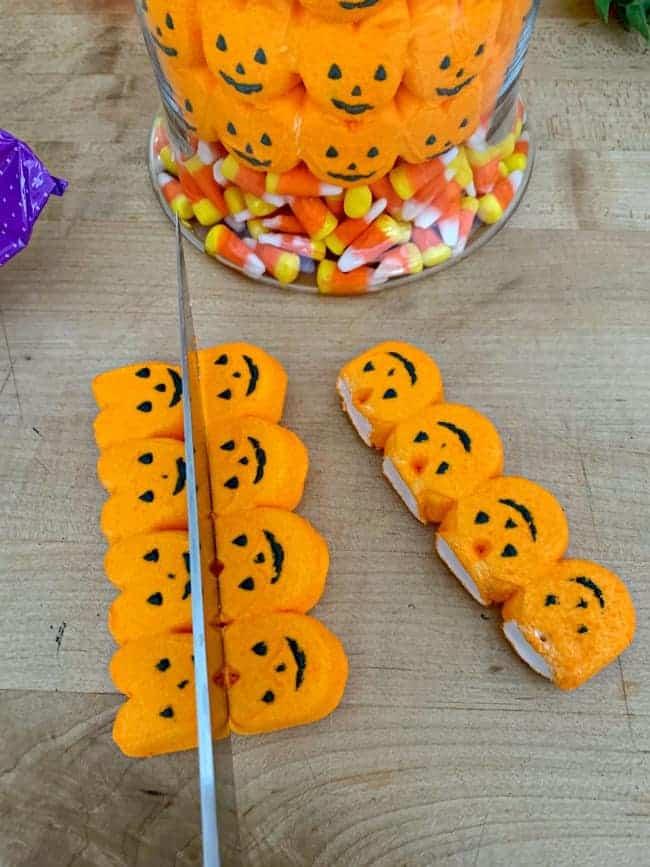 cutting pumpkin marshmallow Peeps with a knife for fall halloween candy centerpiece DIY