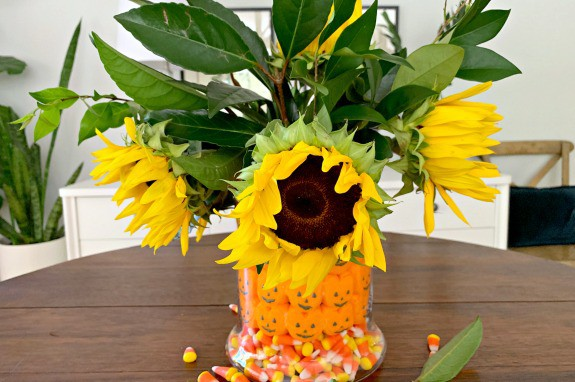 fall candy centerpiece with sunflowers in middle of table