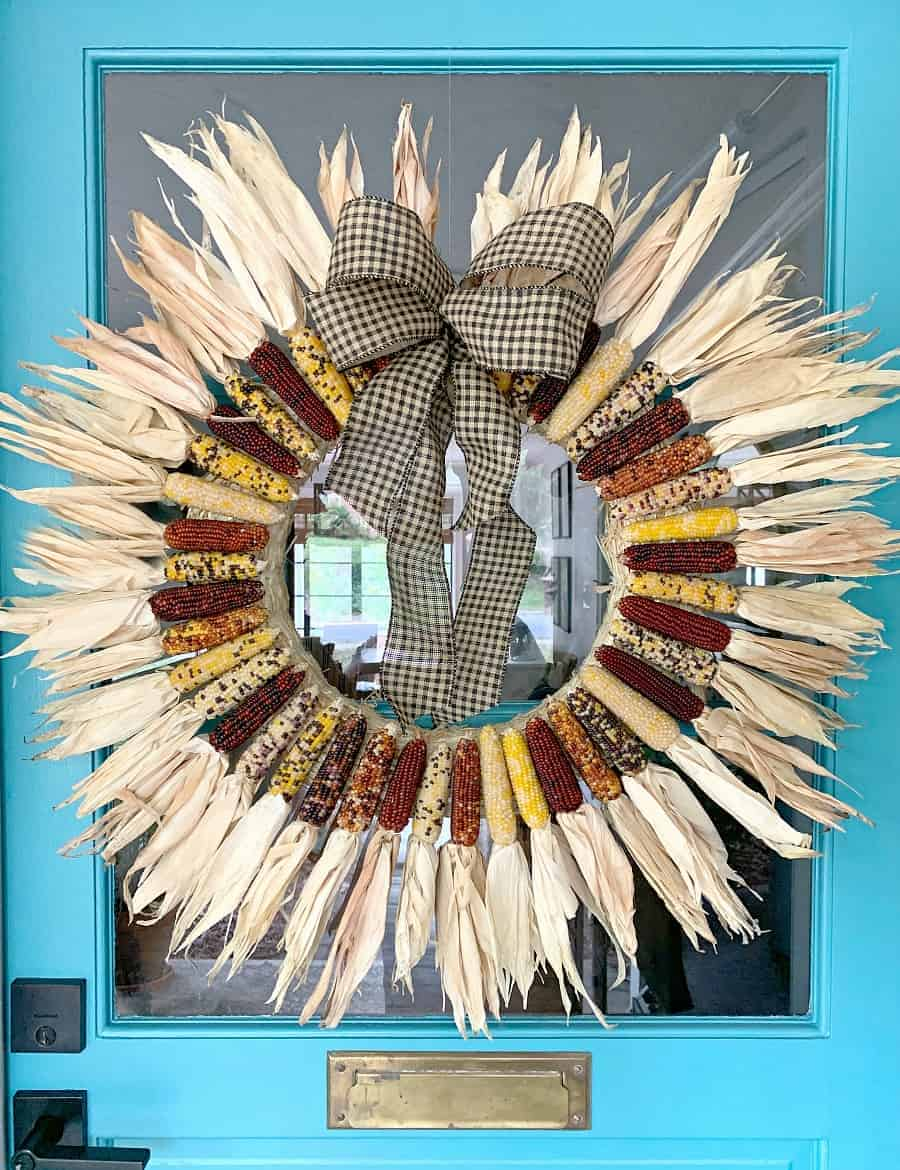 Indian corn wreath hanging on turquoise front door