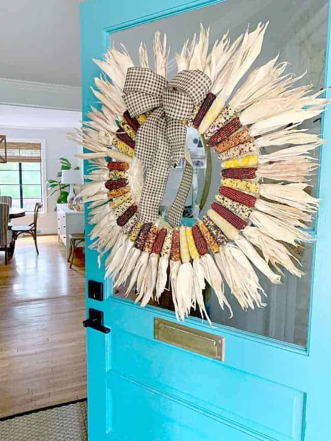 mini Indian corn wreath hanging on turquoise front door