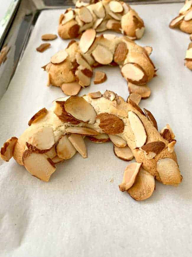 freshly baked almond horn cookies cooling on a parchment paper cookie sheet