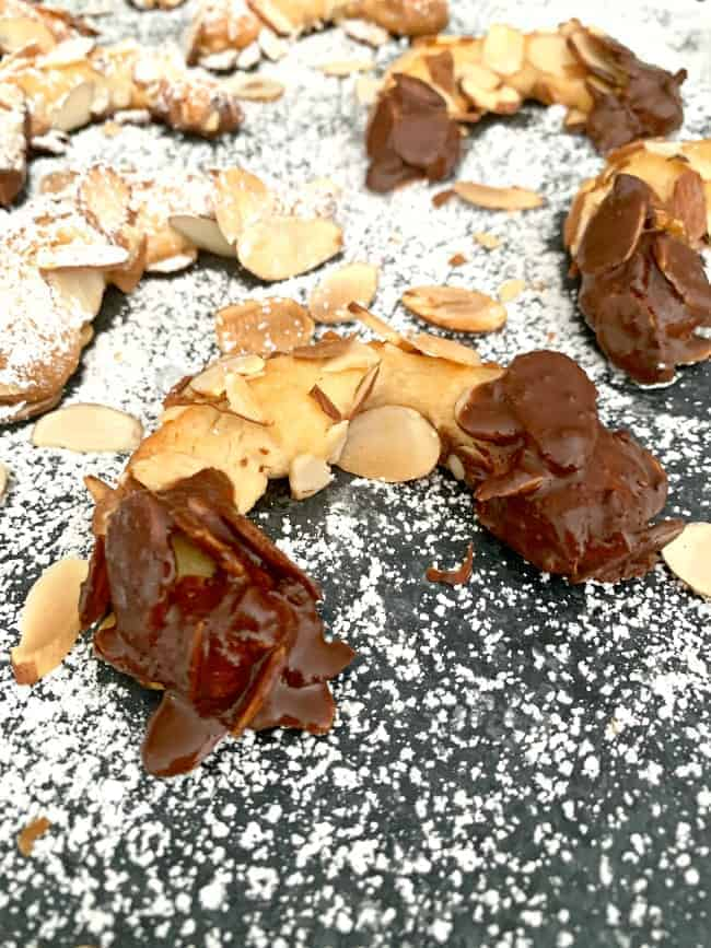 chocolate dipped almond horn cookies on powdered sugar board