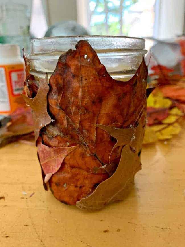 fall leaves glued onto a mason jar candle