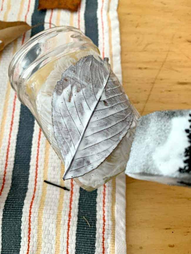 applying mod podge on leaf and mason jar
