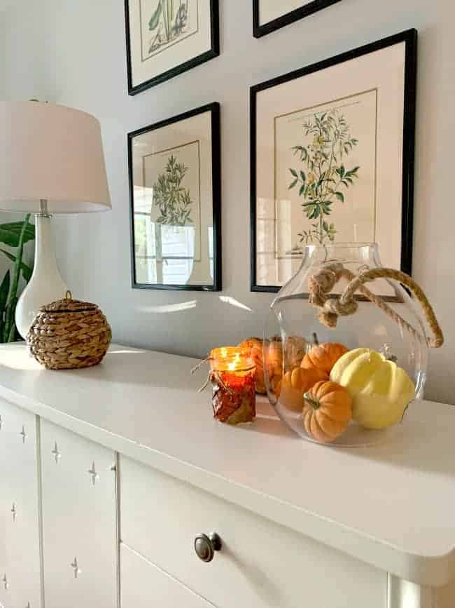 white cabinet with fall leaf candle holders, pumpkins and white lamp