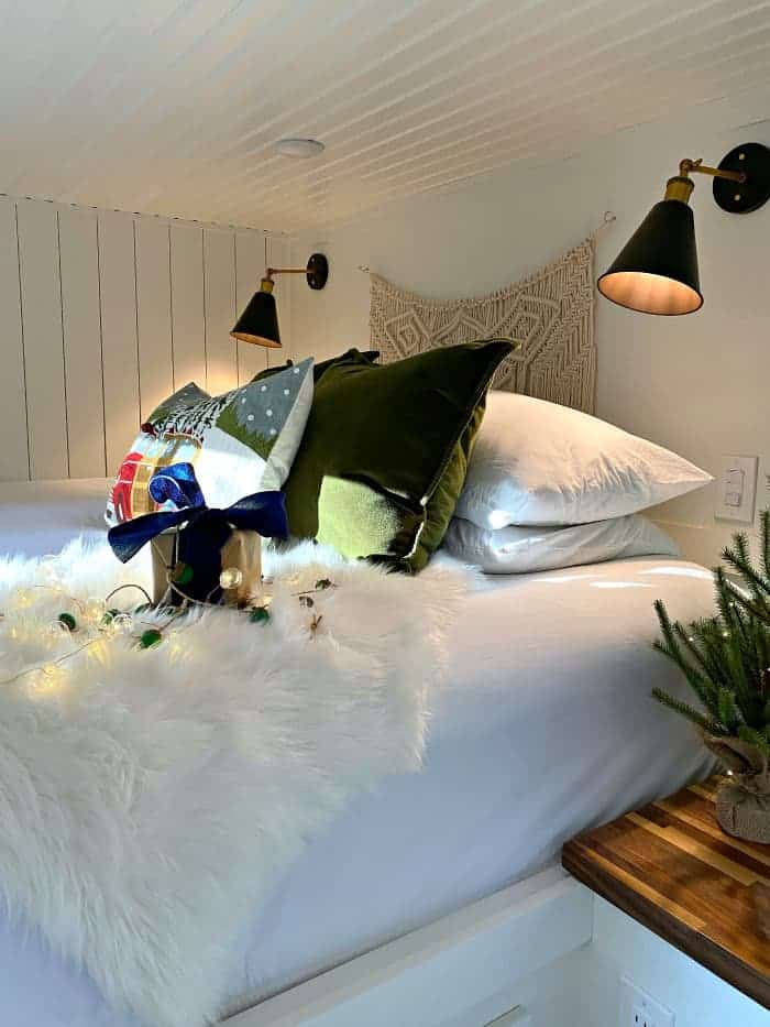 Christmas pillows on bed with faux fur throw