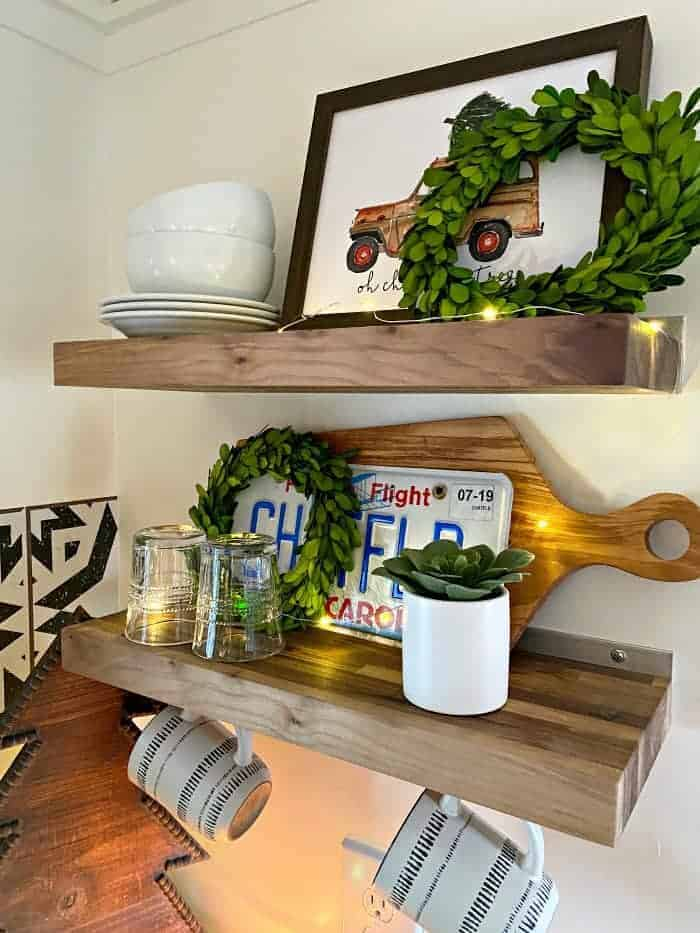 wood shelves in RV decorated for Christmas with wreaths and twinkle lights