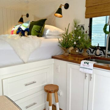 faux Christmas trees on butcher block counter and Christmas pillows on RV bed