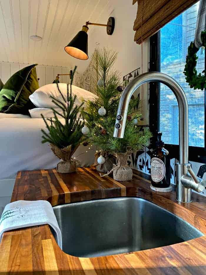 view of RV sink and faux Christmas trees on wood counter