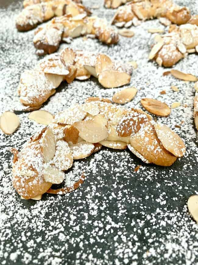 almond horn cookies on black board with powdered sugar sprinkled on top