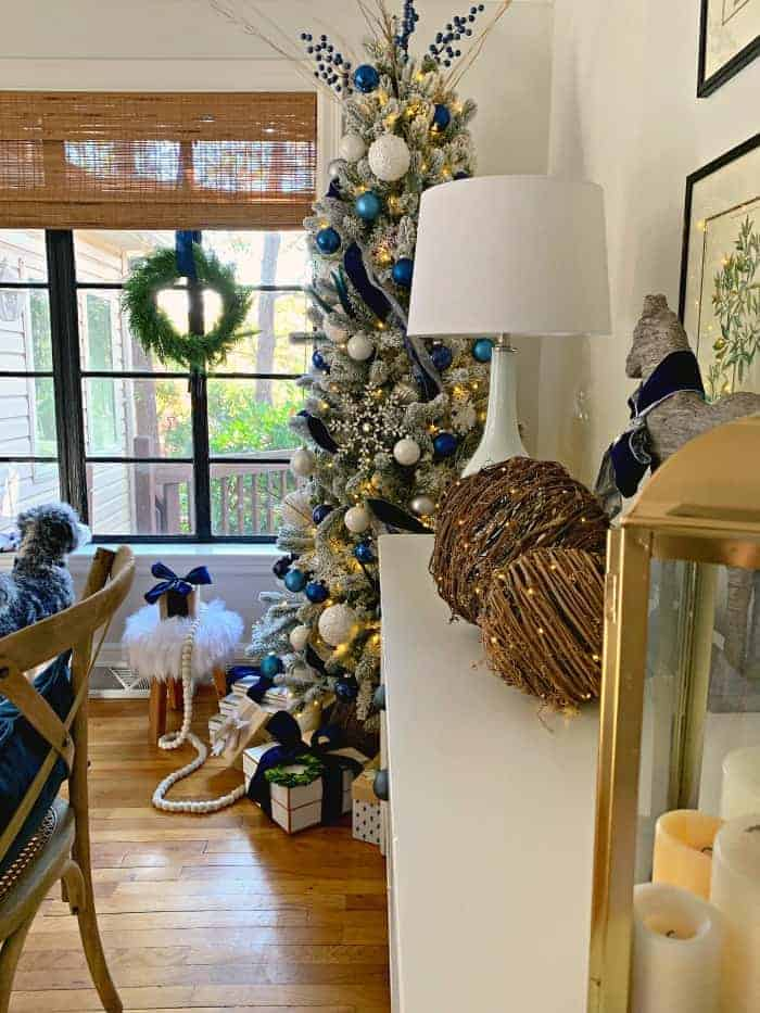 Navy Christmas tree in corner of cottage dining room with presents underneath