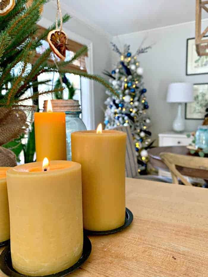 grouping of beeswax candles on kitchen island with navy Christmas tree in the background