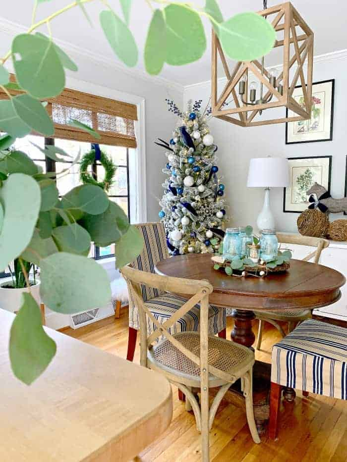 Navy blue Christmas decor and Christmas tree in dining room with round wood table