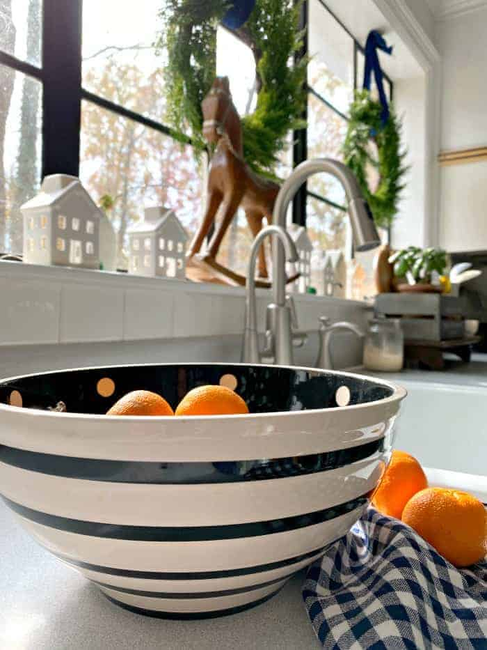 oranges in black and white stripe bowl on kitchen counter