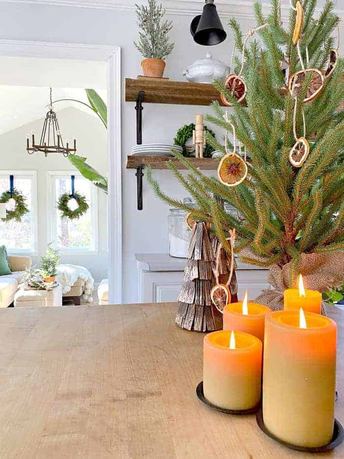 view of faux Christmas tree with dried orange ornaments and grouping of beeswax candles