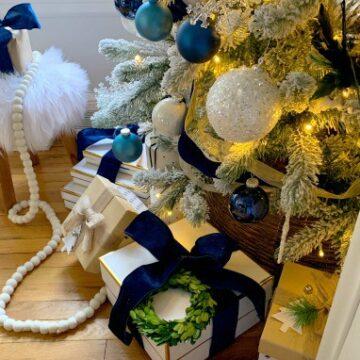 Christmas presents wrapped in velvet ribbon under flocked Christmas tree