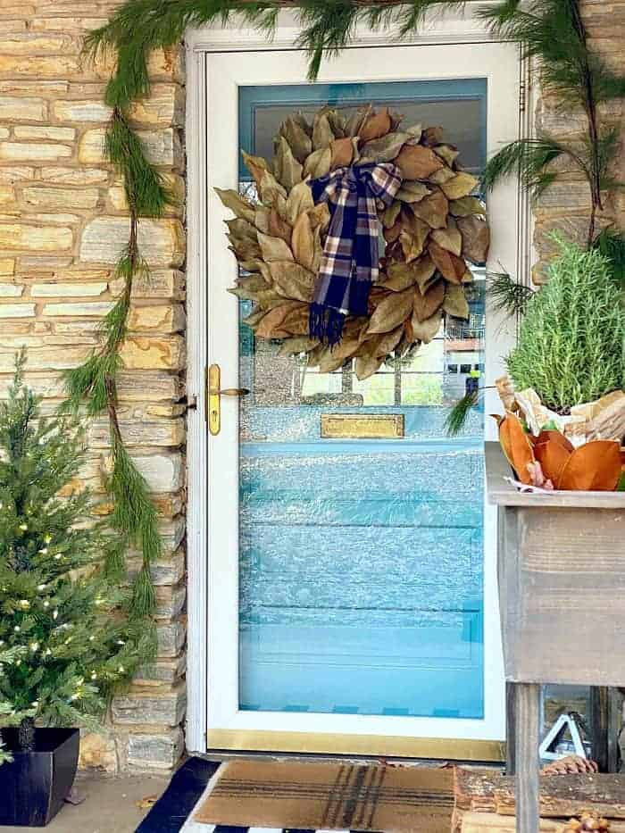 view of front door decorated for Christmas with magnolia leaf wreath
