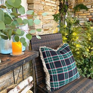 woven chair with black and green pillow on front porch decorated for Christmas
