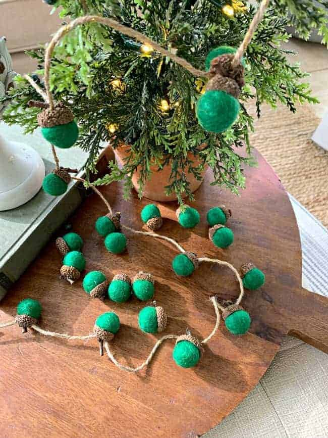 overview of felted green acorn garland on cutting board
