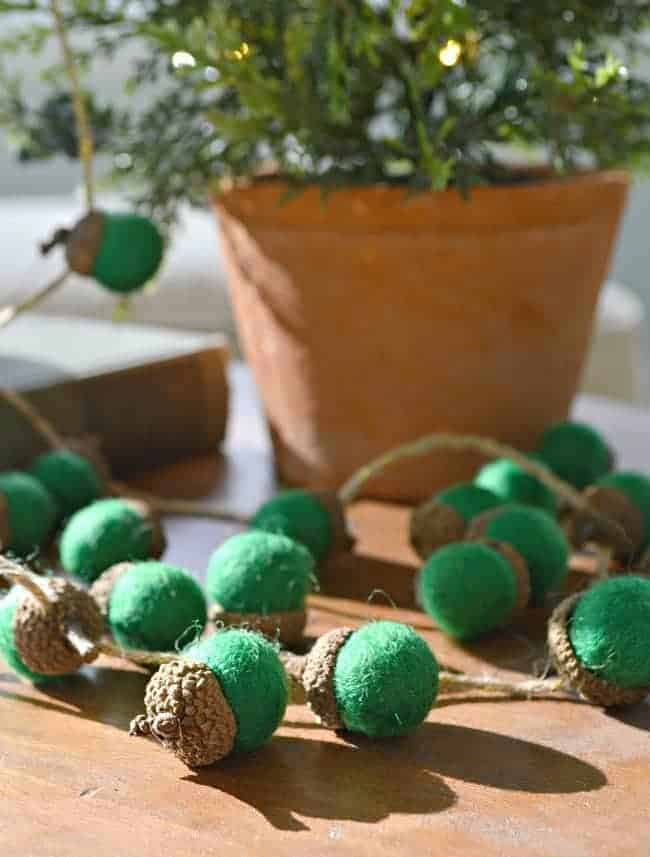 felted green acorn garland on cutting board