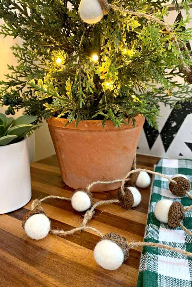 white felted acorn garland laying at the base of a potted faux tree