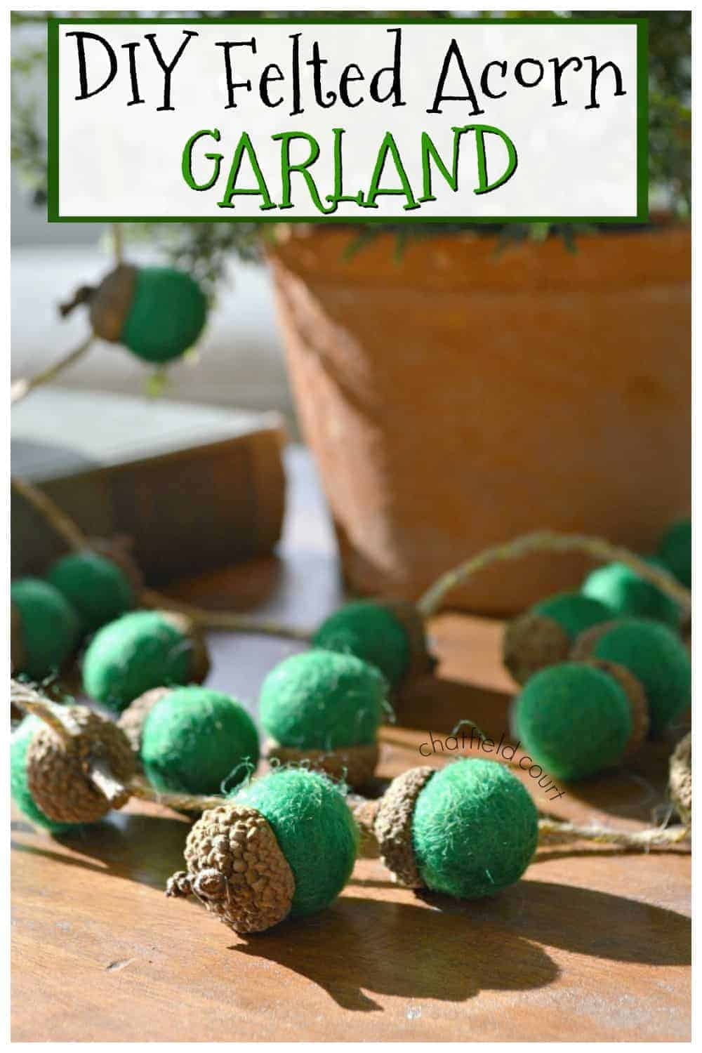 felted green acorn garland on cutting board with large graphic
