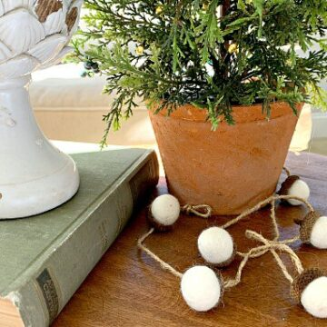 felted acorn garland laying at base of a tiny tree