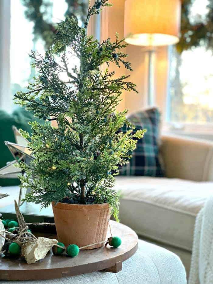 mini faux Christmas tree on ottoman in sunroom