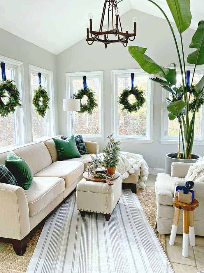 sunroom decorated for Christmas with wreaths hanging in windows