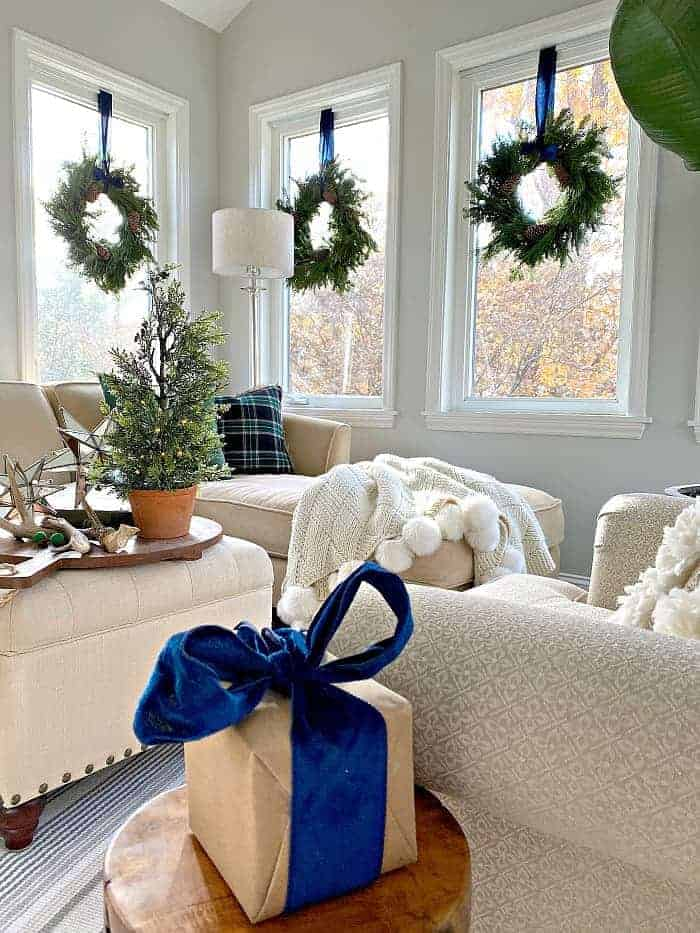 navy blue Christmas decor and wreaths hanging on windows in sunroom