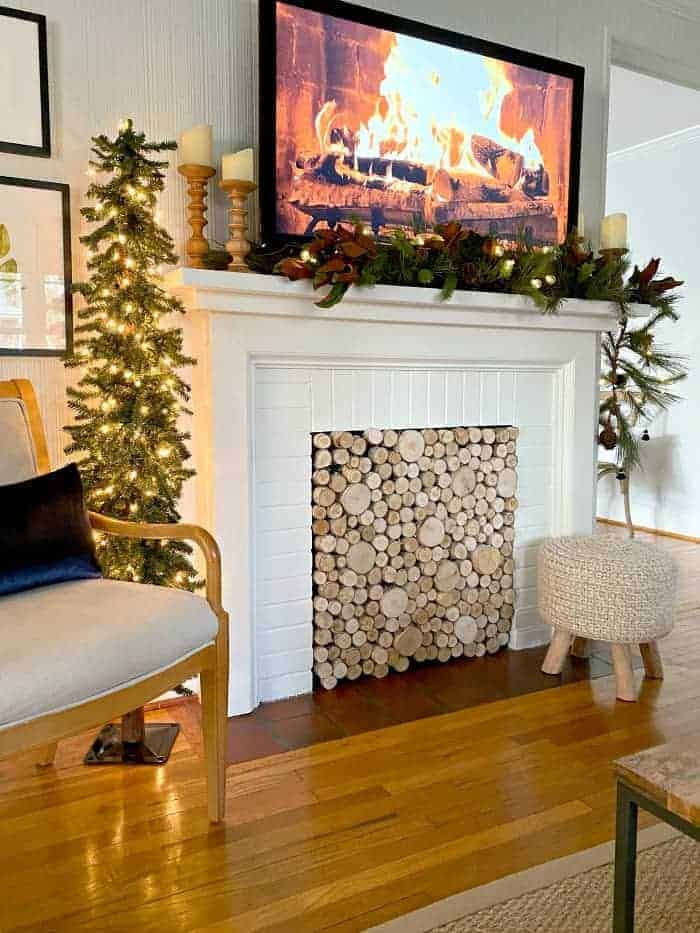 view of Christmas tree and fireplace decorated for Christmas with garland and a fire burning on the tv screen