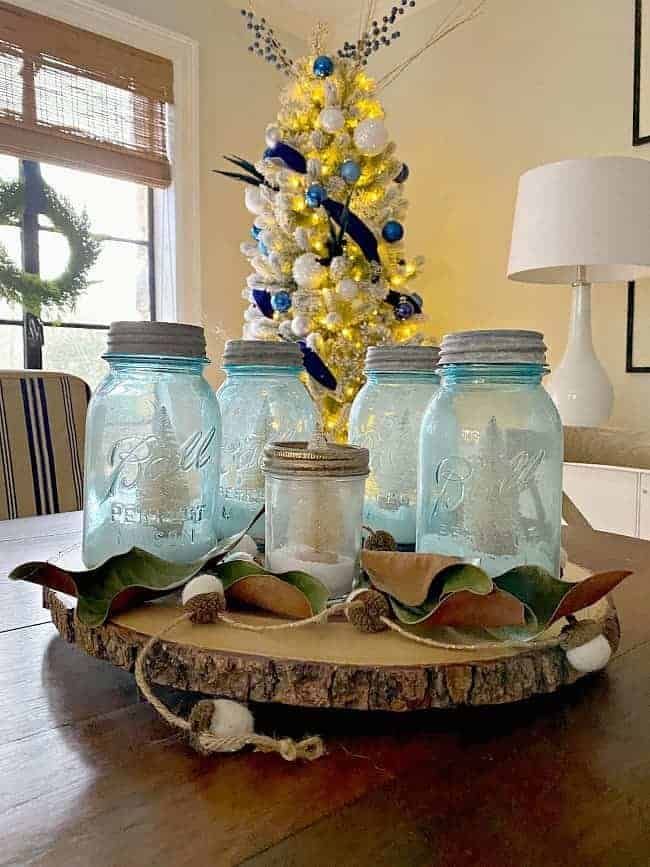 DIY mason jar Christmas centerpiece on dining table with tree in background