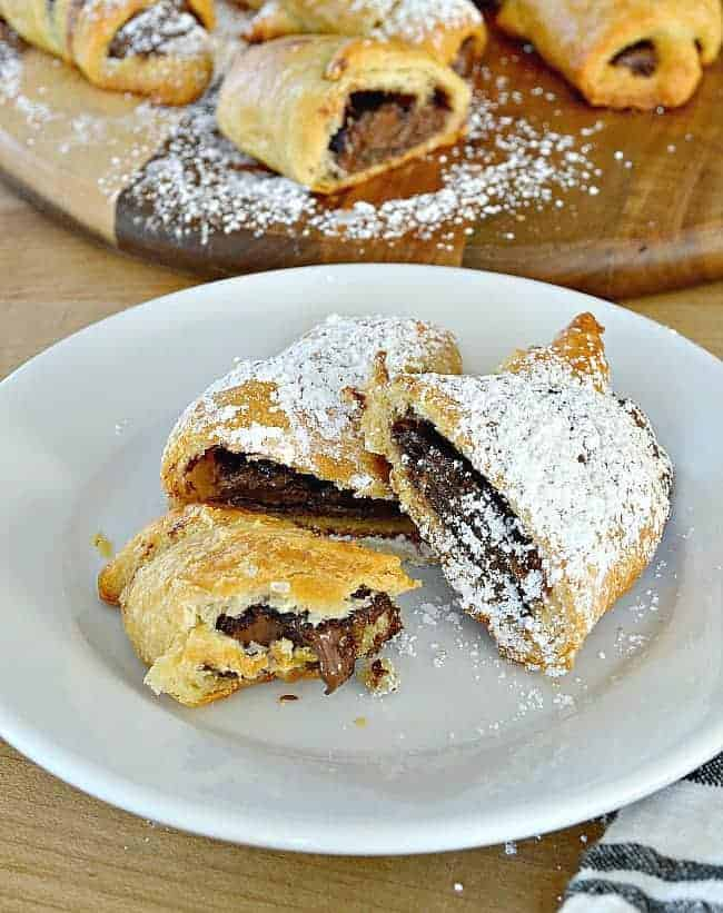 sliced nutella crescent rolls with powdered sugar on white plate