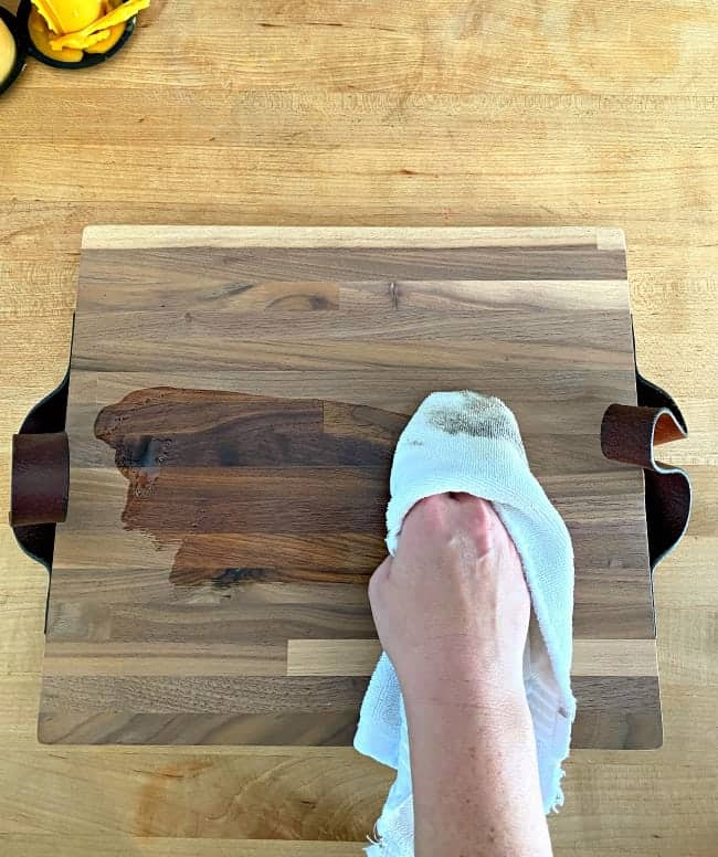 wiping wood conditioner on butcher block cutting board with white cloth