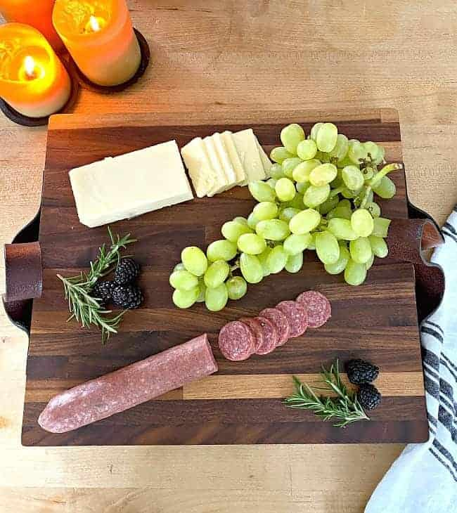 sliced meat and cheese, a bunch of grapes and blackberries on top of DIY butcher block cutting board