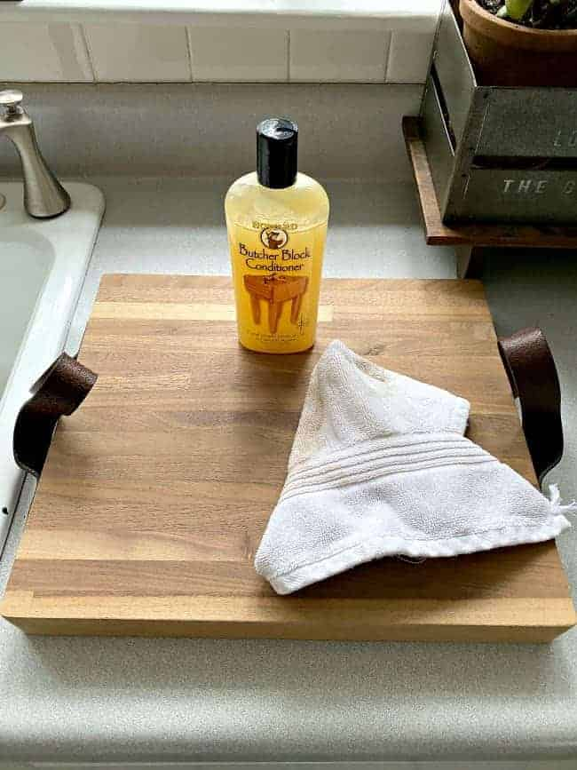 wood conditioner and clean cloth on top of butcher block cutting board