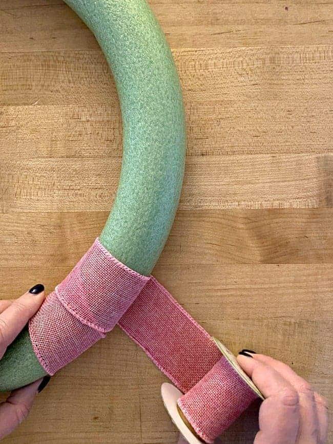 wrapping pink burlap ribbon around green foam wreath form