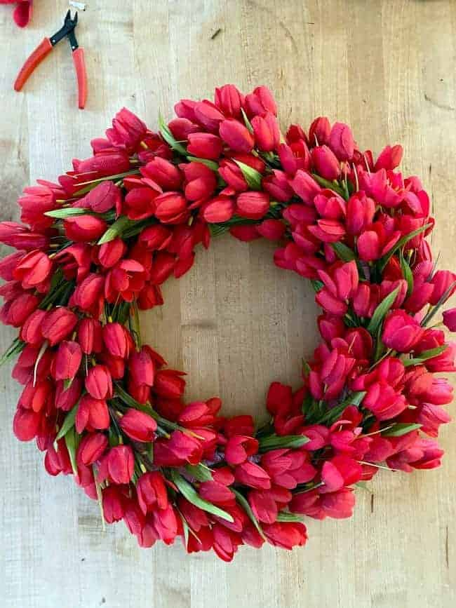 overhead view of faux red tulip wreath on butcher block