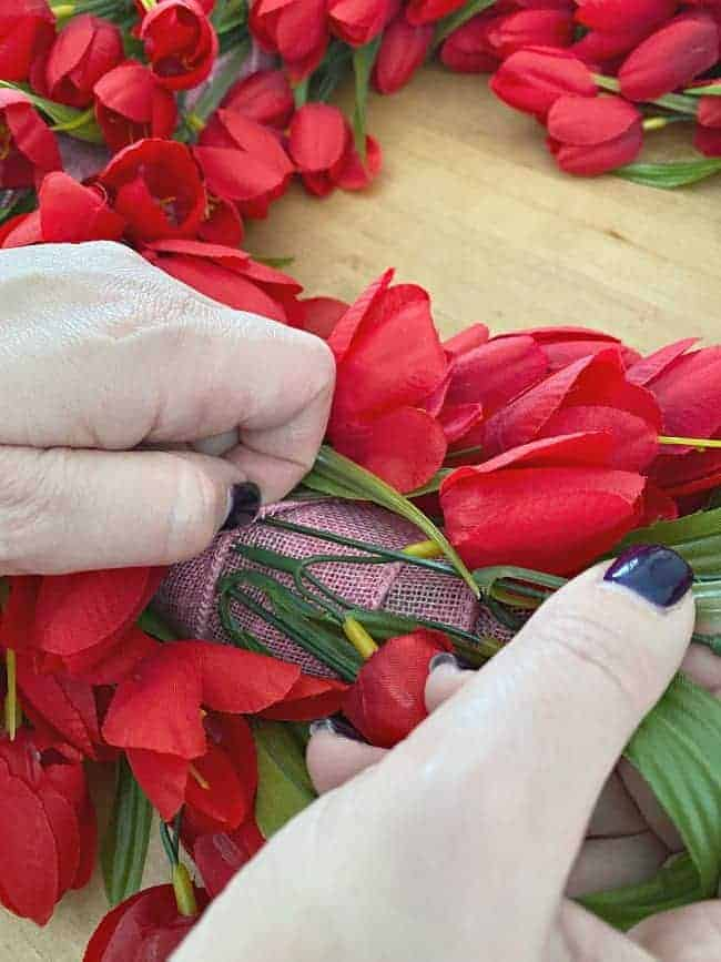 sticking stem of faux tulip into ribbon wrapped wreath form