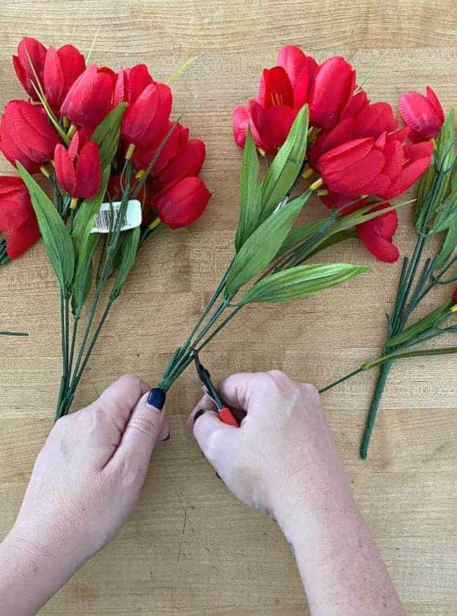 cutting faux red tulips with wire cutters