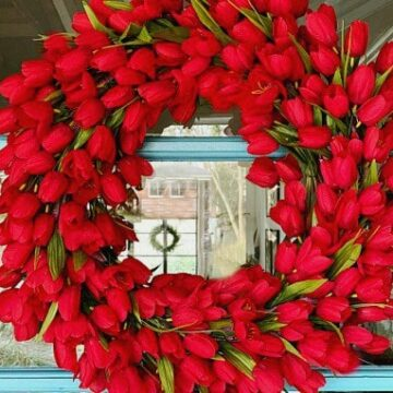 faux red tulip wreath hanging on turquoise painted front door