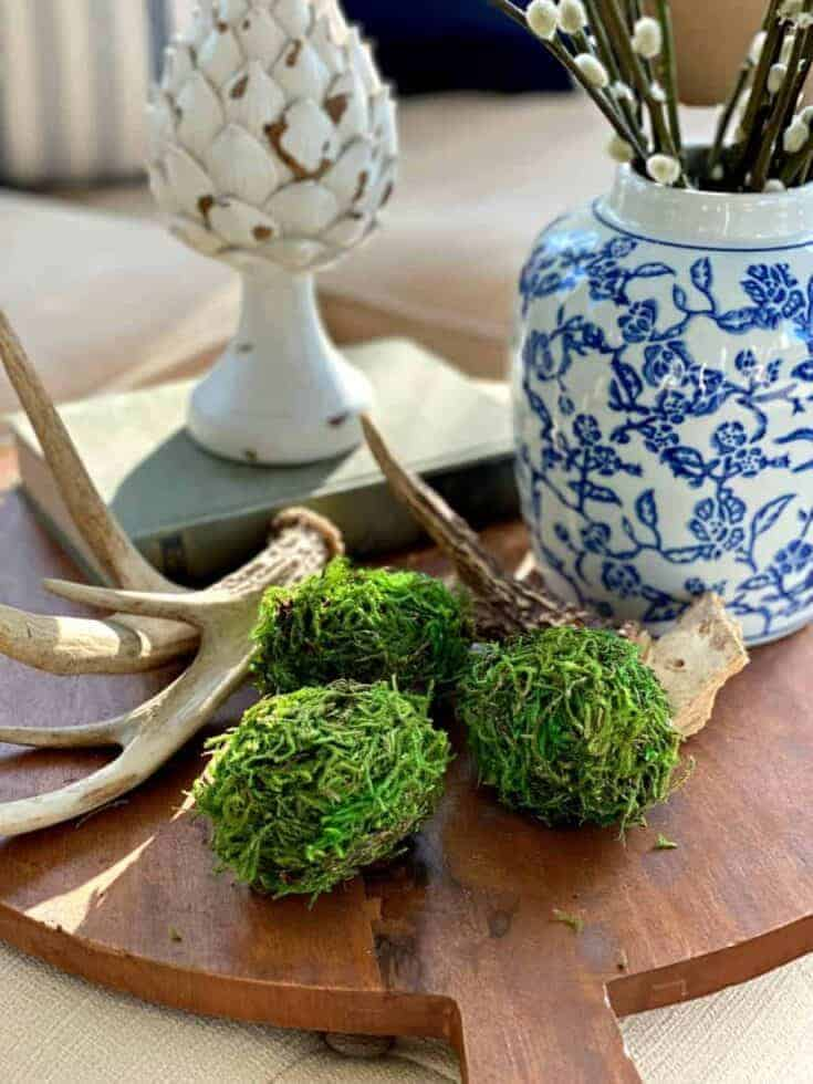 3 DIY moss covered Easter eggs on a wood cutting board with antlers