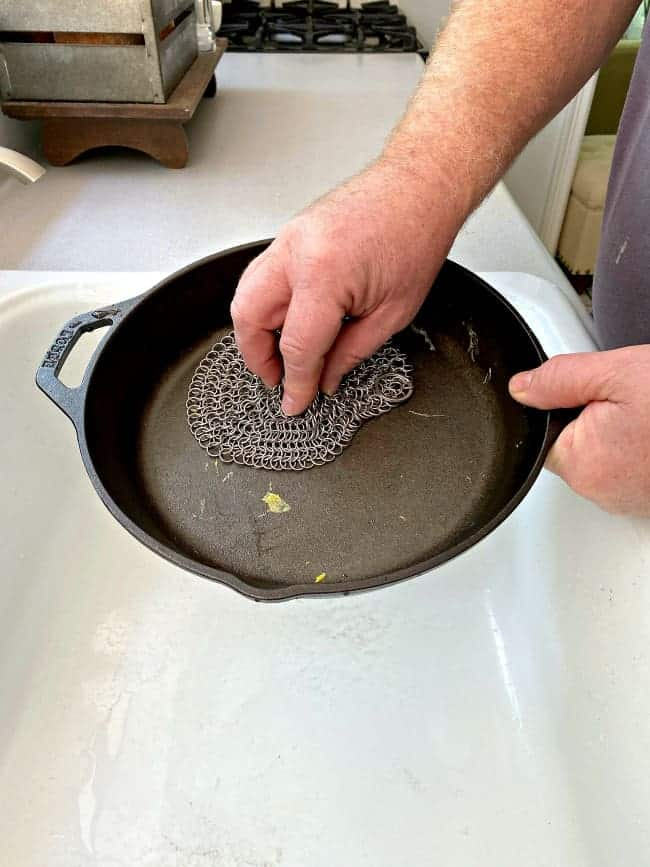 scrubbing a dirty cast iron pan with a scrubber