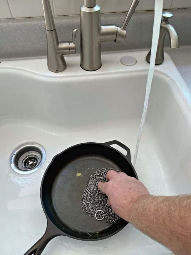 cleaning a dirty cast iron pan in a sink with running water